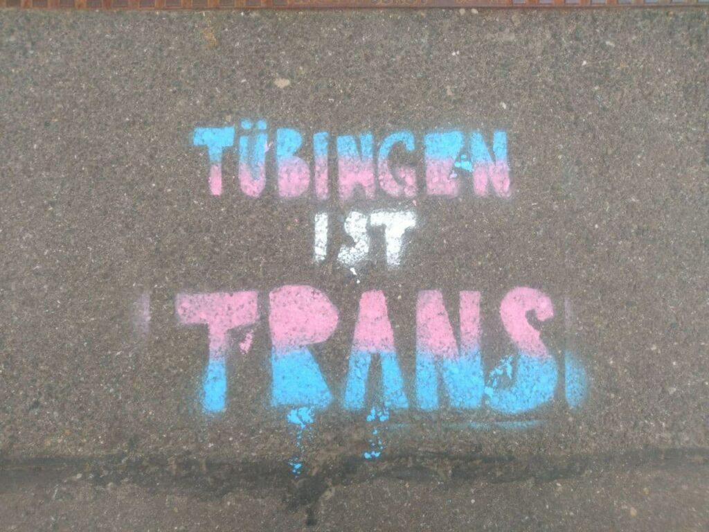 """Bildbeschreibung: Auf Asphaltboden ist mittig ein Schriftzug gesprüht. Er trägt die Farben der trans-Flagge und sagt """"Tübingen ist trans""""."""